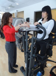The EasyStand Glider has moveable handles that generate reciprocal foot pedal movement. Good Shepherd's Optimal Fitness Center uses the glider to increase the client's range of motion and strength. Pictured: Cynthia Bauer, PT, DPT, OCS, and Optimal Fitness client Ruth Aragon.